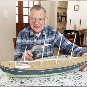Charlie Hall trabajando en su último modelo de barco.  Escala de barcos: una pulgada equivale a 12 pies.  A menudo se coloca una persona esculpida a bordo para ayudar a definir el tamaño del barco.